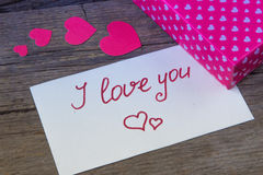 I love you handwritten on white paper and hearted gift box Stock Photos