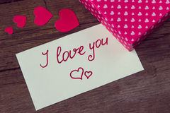 I love you handwritten on white paper and hearted gift box Royalty Free Stock Photos