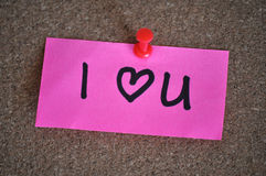 I Love You Heart Note on Pinboard. I (heart) U written on a bright pink post-it note in black marker pen, pinned to a pinboard with a red thumb tac Royalty Free Stock Image