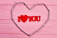 I love you inscription on pink wood. Shape of heart from framing nail on colorful wooden background. Happy Valentines Day Stock Image