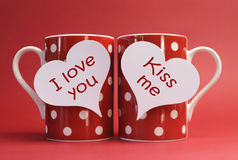 I love you and kiss me messages on red polka dot mugs. Against a red background for a bright, fun and cheerful Valentines Day Royalty Free Stock Images