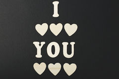 I love you with letters and wooden hearts on black background. Royalty Free Stock Images
