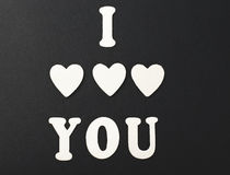 I love you with letters and wooden hearts on black background. Royalty Free Stock Photo