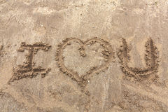 I love you message. Message reading I love you written on the sand Royalty Free Stock Photo
