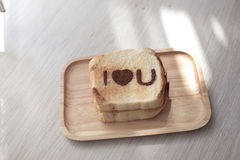 I love you message on toasted on wooden table. Royalty Free Stock Photos