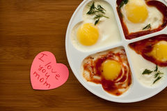 I love you mom. Fried eggs and note I love you mom on wooden table Stock Photos