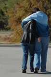 I love you mom. Son hugging his mom as they walk Stock Images
