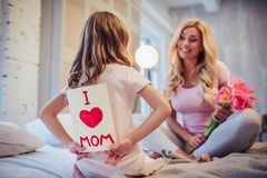 Mom and daughter at home. I love you, mom! Attractive young women with little cute girl are sitting on bed and spending time together at home. Mom is receiving Royalty Free Stock Image