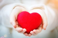 I love you Mom, Mother`s Day. Red heart in hands of the little girl. Symbol of love and family. Selective focus Stock Photography