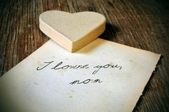 I love you, mom written on an old sheet of paper, with a retro e. A cardboard heart and and old sheet of paper with the tex I love you, mom written in it on a Royalty Free Stock Image