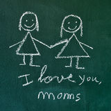 I love you, moms. The sentence I love you, moms handwritten with chalk in a chalkboard, with a drawing of a lesbian couple Stock Photos