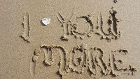 I Love you more. Text i love you more written in the sand on the beach with a hearthstone Stock Image
