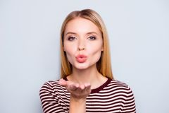 I love you my darling! Close up portrait of beautiful cute lovel. Y charming happy woman clothed in striped outfit, she is sending an air kiss, isolated on grey Royalty Free Stock Image