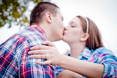 I Love You and My Ring. A young men and women wearing colorful plaid shirts kissing. The young woman's engagement ring is in the foreground Stock Photos