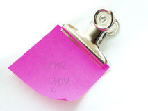 I love you note. Buldog clip holding note with I love you written on it Stock Photo