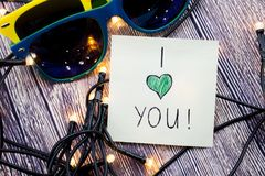 I love you note, Glasses having yellow and blue colors and Lights present in this picture. Love for a particular person or any obj. I love you note Glasses stock photos