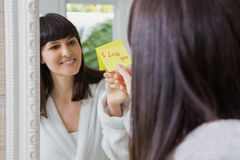 I love you note on mirror. Woman sticking I love you word sticky note on mirror Royalty Free Stock Photo