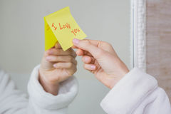 I love you note on mirror. Woman sticking I love you word sticky note on mirror Stock Image