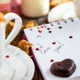 I love you note in the Valentine Day Settings. With Rose Petals, Confetti Hearts, Cup of Hot Chocolate and Chocolate Sweets Royalty Free Stock Photo