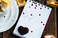 I love you note in the Valentine Day Settings. With Rose Petals, Confetti Hearts, Cup of Hot Chocolate and Chocolate Sweets Royalty Free Stock Photography