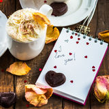 I love you note in the Valentine Day Settings. With Rose Petals, Confetti Hearts, Cup of Hot Chocolate and Chocolate Sweets Stock Image