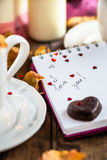 I love you note in the Valentine Day Settings. With Rose Petals, Confetti Hearts, Cup of Hot Chocolate and Chocolate Sweets Royalty Free Stock Photos