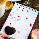 I love you note in the Valentine Day Settings. With Rose Petals, Confetti Hearts, Cup of Hot Chocolate and Chocolate Sweets Royalty Free Stock Images