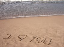I Love You on sandy beach. I Love You sentence written on sandy beach with ocean full of waves in the background. The word Love is replaced by a symbol of heart royalty free stock photography