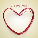 I love you. Sentence I love you and a heart-shaped roll of wire on a beige background, with a retro effect Stock Photo