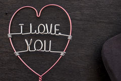 I Love you. Sentence I love you and a heart-shaped roll of wire on a black lining background Royalty Free Stock Photo