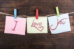 I love you note. I love you in sticky notes hanging by clothespin on wood Stock Photo
