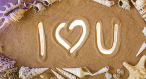 I Love You symbol in the sand. Beach background. Top view. Romantic concept: I love U icon is Highlighted by Rays of Light. Beautiful Romantic Sandy Background royalty free stock photo