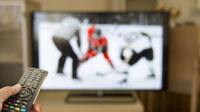 whatcing hockey game on home tv royalty free stock photography