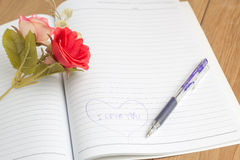 I love you text in notebook with pen and fake flower Stock Photos