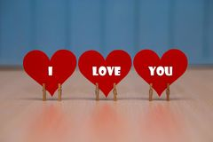 `I love you` text on red paper heart on table. With blue wooden background royalty free stock photos
