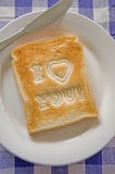 I Love You Toast. I love you message on toasted white bread on a plate with a knife royalty free stock photos