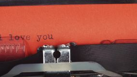 I love you - typed on a old vintage typewriter. Printed on red paper. The red paper is inserted into the typewriter.  stock footage