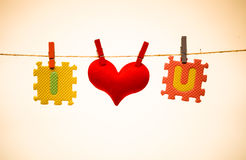 I love you. Love for Valentine's day - Red heart with I and u jigsaw hung on a rope royalty free stock photography