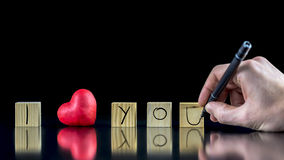 I Love You. Valentines concept with a man writing with a pen on wooden blocks - I Love You - with a symbolic red heart depicting his Love and commitment Stock Photo
