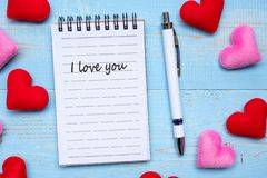 I LOVE YOU word on note book and pen with red and pink heart shape decoration on blue wooden table background. Love, Wedding,. Romantic and Happy Valentine royalty free stock images
