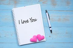 I LOVE YOU word on notebook and pen with couple pink heart shape decoration on blue wooden table background. Wedding, Romantic and. Happy Valentine' s royalty free stock photo