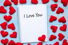 I LOVE YOU word on notebook with pink heart shape decoration on blue wooden table background. Wedding, Romantic and Happy. Valentine' s day holiday stock photos