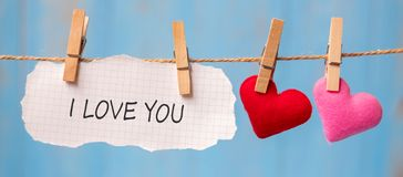 I LOVE YOU word on paper and couple heart shape decoration hanging on line with copy space for text on blue wooden background. Love, Wedding, Romantic and royalty free illustration