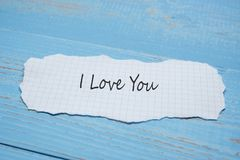 I LOVE YOU word on paper note on blue wooden table background. Wedding, Romantic and Happy Valentine' s day holiday concept. I LOVE YOU word on paper note royalty free stock image