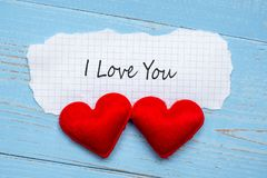 I LOVE YOU word on paper note with couple red heart shape decoration on blue wooden table background. Wedding, Romantic and Happy. Valentine' s day stock image