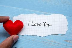 I LOVE YOU word on paper note with red heart shape decoration on blue wooden table background. Wedding, Romantic and Happy. Valentine' s day holiday stock photo