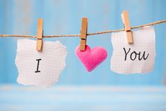 I LOVE YOU word on paper and pink heart shape decoration hanging on line with copy space for text on blue wooden background. Love. Wedding, Romantic and Happy stock illustration