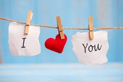 I LOVE YOU word on paper and red heart shape decoration hanging on line with copy space for text on blue wooden background. Love,. Wedding, Romantic and Happy royalty free illustration