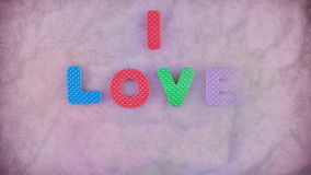 I Love You. Words I Love You appearing letter by letter on the pink texture for background. Different color letters stock video footage