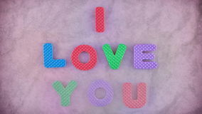 I Love You. Words I Love You appearing word by word on the pink texture for background. Different color letters and pink background become red in the end on the stock video footage